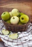 Nya äpplen i korg på tabellen Royaltyfria Foton