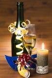 Nya år dagstilleben med champagneflaskan, exponeringsglas och den brännande stearinljuset Fotografering för Bildbyråer