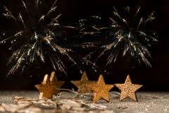 Nya år Ev - guld- stjärnor i snön, i bakgrunden av en mörk natt och fyrverkerier royaltyfria foton
