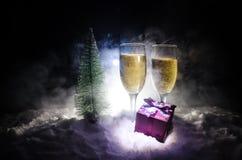 Nya år helgdagsaftonberömbakgrund med par av flöjter och flaskan av champagne med julträdet på snö på mörk bakgrund Arkivfoto