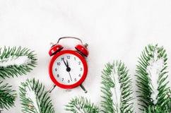 Nya år klocka och snö-täckte granfilialer Arkivfoton