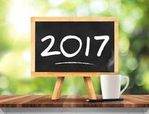 2017 nya år på svart tavla med kaffekoppen, blyertspenna på plankaträ Royaltyfri Foto