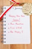 Nya år upplösningar som är skriftliga i anteckningsbok och guldmedalj Arkivfoto