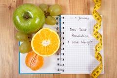 Nya år upplösningar som är skriftliga i anteckningsbok och måttband Arkivbilder