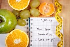 Nya år upplösningar som är skriftliga i anteckningsbok och måttband Arkivfoto