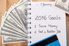 Nya år upplösningar som är skriftliga i anteckningsbok, valutor dollar och kreditkort Arkivfoton