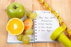 Nya år upplösningar som är skriftliga i anteckningsboken och frukter, hantlar med cm Royaltyfria Foton