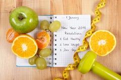 Nya år upplösningar som är skriftliga i anteckningsboken och frukter, hantlar med cm Arkivfoton