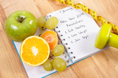 Nya år upplösningar som är skriftliga i anteckningsboken och frukter, hantlar med cm Royaltyfri Bild