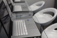 Nya öppna bärbara datorer, på ett glass skrivbord; moderna vitstolar i bakgrund Arkivfoto
