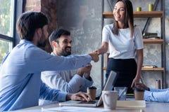 Nya affärspartners Unga moderna kollegor i smarta tillfälliga kläder som skakar händer och ler, medan sitta i arkivfoton