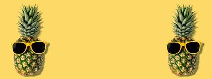 Nya ananors med solglas?gon p? gul bakgrund Id?rikt suumerbegrepp royaltyfria foton