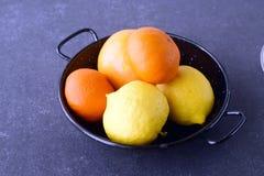 Nya apelsiner, citroner och mandarines på en grå färg gör sammandrag bakgrund Medelhavs- livsstil sund mat Arkivbilder