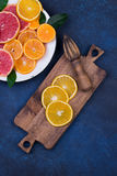 Nya apelsiner, grapefrukter och madarineskivor på mörk stenbakgrund Royaltyfri Fotografi