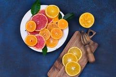 Nya apelsiner, grapefrukter och madarineskivor på mörk stenbakgrund Royaltyfri Foto