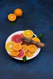Nya apelsiner, grapefrukter och madarineskivor på mörk stenbakgrund Arkivfoto