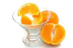 Nya apelsiner i exponeringsglaset på vit bakgrund Arkivbild
