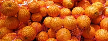 Nya apelsiner i plast- ingreppssäck på hyllan i lagret arkivbild
