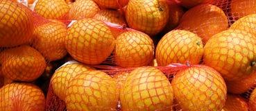 Nya apelsiner i plast- ingreppssäck på hyllan i lagret arkivbilder