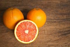 Nya apelsiner med skivor på träbakgrund Arkivbild