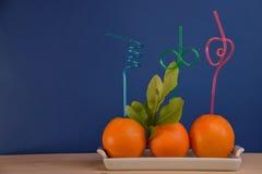 Nya apelsiner med utsmyckade färgrika sugrör Arkivbild