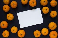 Nya apelsiner och tomt kort på svart bakgrund Apelsiner och tomt kortfoto Royaltyfri Bild
