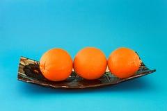 Nya apelsiner på en blå maträtt arkivfoton