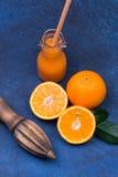 Nya apelsiner, träsquezzer och flaska av ny orange fruktsaft på mörk stenbakgrund Arkivfoto
