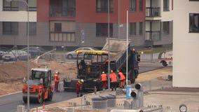 Nya arbetare för pavers för vägkonstruktion och special utrustning arkivfilmer