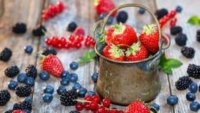 Nya bär - grotesk hink som är full med jordgubbar arkivfoton