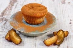 Nya bakade muffin med plommoner och kanel i pulverform på plattan, läcker efterrätt Fotografering för Bildbyråer