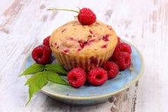 Nya bakade muffin och hallon på plattan på gammal träbakgrund, läcker efterrätt Royaltyfria Bilder