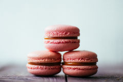 Nya bakade purpurfärgade rosa macarons för makronbakelsekakor, makaroni i detaljistskärm, slut upp, sikt för låg vinkel Royaltyfri Bild