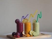 Nya banan-, spenat- och apelsinsmoothies på trätabellen Arkivfoton