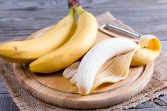 Nya bananer och skalad banan på ett träbräde Royaltyfri Foto