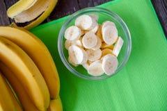 Nya bananer och skivad banan i bunken, bästa sikt Arkivbild