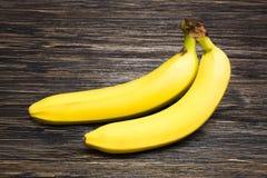 Nya bananer på träbakgrund Arkivbilder