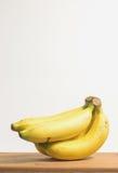 Nya bananer på trävit bakgrund royaltyfri fotografi