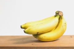 Nya bananer på trävit bakgrund royaltyfria bilder
