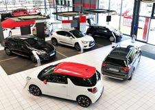 Nya bilar i försäljningsområdet av en bilåterförsäljare - byggnad och ar Arkivfoto
