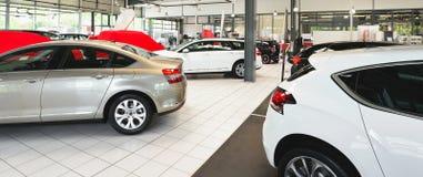 Nya bilar i försäljningsområdet av en bilåterförsäljare - byggnad och ar Royaltyfria Bilder