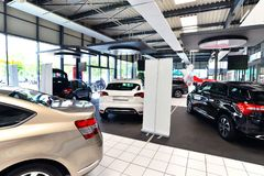 Nya bilar i försäljningsområdet av en bilåterförsäljare - byggnad och ar Royaltyfri Foto