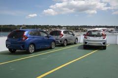 Nya bilar på däck av en färja Royaltyfria Bilder