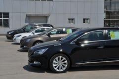 Nya bilar utanför en bilåterförsäljare Arkivfoto
