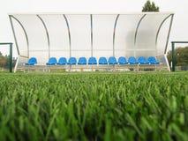 Nya blåa plast- platser på utomhus- stadionspelarebänk, stolar med ny målarfärg nedanför det genomskinliga böjda plast- taket Arkivbilder