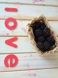 Nya blåbär i korg med förälskelsemeddelandet Arkivfoton