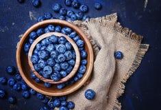Nya blåbär i träbunke på blå bakgrund, bästa sikt royaltyfri bild