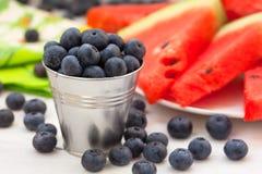 Nya blåbär med vattenmelonskivor royaltyfria foton