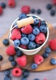 Nya blåbär och hallon i en hink Royaltyfri Fotografi