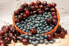 Nya blåbär och körsbär Arkivfoto